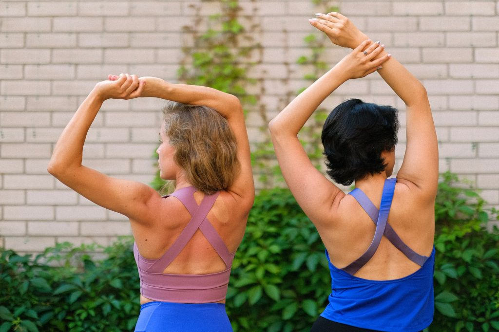 anonymous female friends stretching in yard